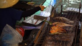 A Thai Woman in Traditional Cloth Cooking Big Shrimps on a Barbecue Fire in the Boat at Floating Market, Bangkok. stock footage