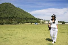 Thai woman travel and posing for take photo on grass field Chang Hua Man Royal Initiative and Agricultural Project Stock Image