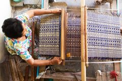Thai woman weaving straw mat. Thai woman weaving traditional straw mat using Cyperus alternifolius stems, Khon Kaen, Thailand royalty free stock photos