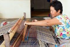Thai woman weaving straw mat. Thai woman weaving traditional straw mat using Cyperus alternifolius stems, Khon Kaen, Thailand royalty free stock photo