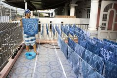 Thai women working Indigenous knowledge of thailand tie batik dyeing indigo color at outdoor on top of house at Thailand. Thai woman working Indigenous knowledge stock photo