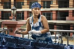 Thai women working Indigenous knowledge of thailand tie batik dyeing indigo color at outdoor on top of house at Thailand. Thai woman working Indigenous knowledge stock images