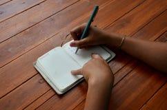 Thai woman write note book Royalty Free Stock Photos