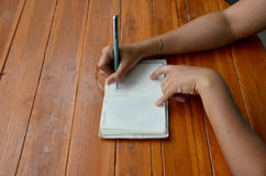 Thai woman write note book Royalty Free Stock Photography
