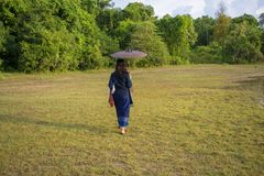 Asian women walking on umbrellas,Thai women walk in the grass. royalty free stock photos