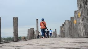 Thai women and burmese travel and walking at U Bein Bridge in Amarapura, Myanmar. U Bein Bridge is a crossing that spans the Taungthaman Lake near Amarapura in stock video footage