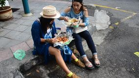 Thai women eating rice topped malaysian curry style