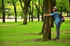 Thai women love and hug tree Stock Photo