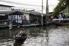 Thai women people rowing and driving wooden boat in small canal Royalty Free Stock Images