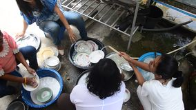 Thai women people wash dishes after eat in party stock footage