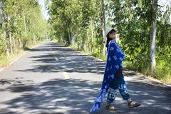 Thai women posing relax and playing indigo tie dye fabric shawl on the small street in countryside stock photo