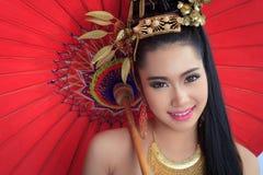 Thai women with red umbrella. Thai woman with red umbrella - studio shot Stock Image