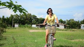 Thai women riding bicycle in the garden. This VDO shooting location at Pattalung province of southern Thailand stock video