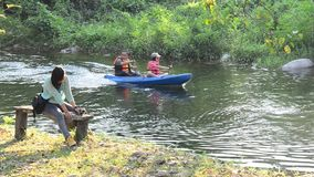 Thai women sit on  bench and traveler paddle kayak or canoe at Suan Phueng stock video footage