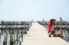 Thai women sitting alone on the walkway bridge in Mangrove forest Royalty Free Stock Image