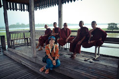 Thai women sitting and talk with Burmese monk at U Bein Bridge Royalty Free Stock Photos