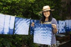 Thai women tie batik dyeing handkerchief indigo color. Thai woman tie batik dyeing handkerchief tie batik indigo color or mauhom color and hanging process dry stock images