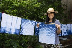 Thai women tie batik dyeing handkerchief indigo color. Thai woman tie batik dyeing handkerchief tie batik indigo color or mauhom color and hanging process dry stock photography