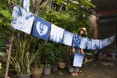 Thai women tie batik dyeing handkerchief indigo color. Thai woman tie batik dyeing handkerchief tie batik indigo color or mauhom color and hanging process dry royalty free stock photography