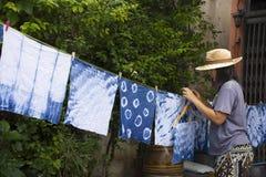 Thai women tie batik dyeing handkerchief indigo color. Thai woman tie batik dyeing handkerchief tie batik indigo color or mauhom color and hanging process dry stock photo