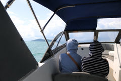 Thai women wear a coat and sitting on speed boat. Royalty Free Stock Photo