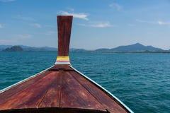 Thai wooden head longtail boat heads toward Stock Photo