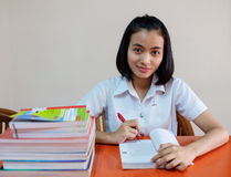 Thai young adult woman student in uniform reading a book Stock Photo