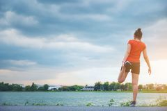 Thai young fitness woman runner stretching legs before run at park. Watwer royalty free stock image
