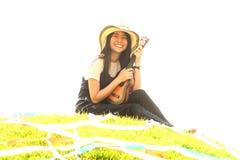 Thai young girl with Ukulele on mound. Royalty Free Stock Photo