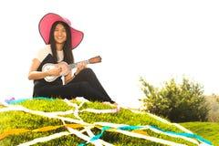 Thai young girl with Ukulele on mound. Royalty Free Stock Photos