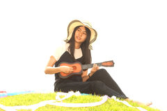 Thai young girl with Ukulele On mound. Stock Images