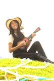 Thai young girl with Ukulele on mound. Royalty Free Stock Photography