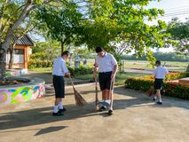 Thai young students in school uniform help together sweeping the cement floor in their school every morning. Hua Hin, Thailand