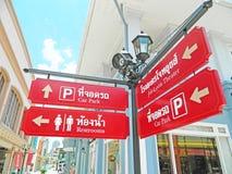 Thailändisch-englischer Sprachwegweiser bei Asiatique die Fluss-Front in Bangkok, Thailand Stockbilder