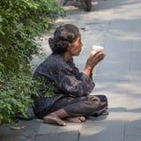 Thailändische alte Bettlerfrau wartet auf Almosen auf einer Straße Stockfoto