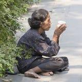 Thailändische alte Bettlerfrau wartet auf Almosen auf einer Straße Stockfotografie