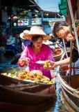 Thailändische Einheimische verkaufen Lebensmittel und Andenken an berühmtem sich hin- und herbewegendem Markt Damnoen Saduak, Tha Stockfotografie