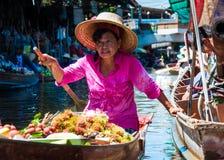 Thailändische Einheimische verkaufen Lebensmittel und Andenken an berühmtem sich hin- und herbewegendem Markt Damnoen Saduak, Tha Lizenzfreie Stockfotos