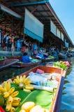 Thailändische Einheimische verkaufen Lebensmittel und Andenken an berühmtem sich hin- und herbewegendem Markt Damnoen Saduak, Tha Lizenzfreie Stockbilder