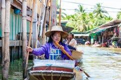 Thailändische Einheimische verkaufen Lebensmittel und Andenken an berühmtem sich hin- und herbewegendem Markt Damnoen Saduak, Tha Stockbild