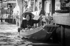 Thailändische Einheimische verkaufen Lebensmittel und Andenken an berühmtem sich hin- und herbewegendem Markt Damnoen Saduak, Tha Lizenzfreies Stockbild