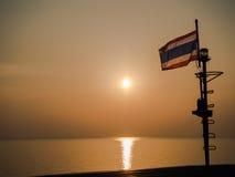 Thailändische Flagge auf dem Meer mit Sonnenuntergangansicht lizenzfreies stockbild