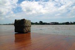 Thailändische Flechtweide des klebrigen Reises gemacht vom Kokosnussblatt gesetzt auf den Holztisch, neben Chaophraya-Fluss stockfotos