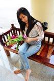 Thailändische Frau, die auf der Bank im Tempel Thailand sitzt Stockfotografie