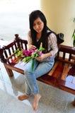 Thailändische Frau, die auf der Bank im Tempel Thailand sitzt Stockfoto