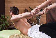 Thailändische Frau, die einem Mann Massage macht Lizenzfreie Stockbilder