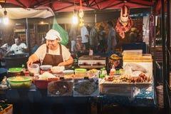 Thailändische Frau, die Papayasalat am Straßenmarkt kocht lizenzfreie stockfotos
