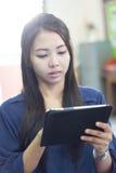 Thailändische Frau, die Tablette verwendet Stockfotografie