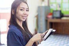Thailändische Frau, die Tablette verwendet Lizenzfreies Stockfoto