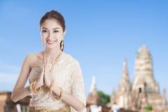 Thailändische Frau im thailändischen Kleiderkostüm traditionell in einer willkommenen Haltung lizenzfreie stockfotografie